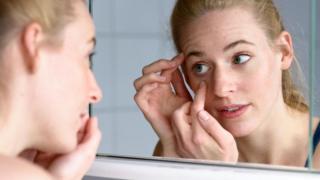 Una mujer se inspecciona los ojos en el espejo