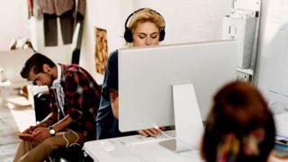 Personas trabajando en una oficina abierta