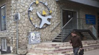 A Kosovar checks his mobile phone as he walks past EU Information and Cultural Office in Kosovo's capital Pristina