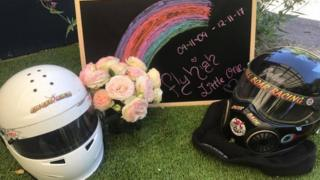Helmets and flowers form a tribute to Anita Board