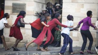 Women are evacuated out of the scene as security officers search for attackers during an ongoing gunfire and explosions in Nairobi, Kenya, 15 January 2019.