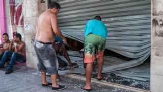 Men fix the broken shutter of their shop after burglars entered in Vila Velha, near Vitoria, eastern Brazil, on 6 February