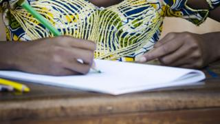An girl at a desk in Africa drawing - stock image