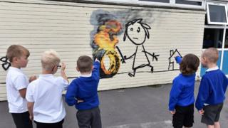 "Children from Bridge Farm Primary School look at a new ""Banksy"" authenticated mural that appeared on the school wall during half term in Withchurch, Britian"