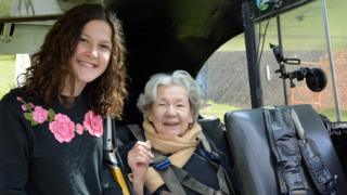 Matilda (L) stands next to the plane and her grandmother Mollie sits in the plane (R)