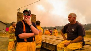 Firefighters take a break from battling a bushfire near the town of Miena in Tasmania