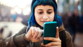 فتاة تتصفح هاتفا ذكيا