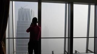 A man takes photos of buildings on a polluted day in Beijing