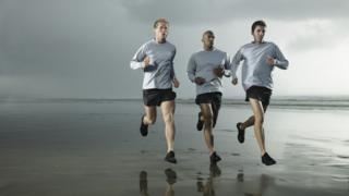 Men jogging on the beach