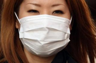 A woman wearing a mask walks past about the outbreak of coronavirus in Wuhan, China at Ginza shopping district in Tokyo, Japan, January 26, 2020. (Photo by Hitoshi Yamada/NurPhoto via Getty Images)