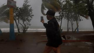 A woman records with her cell phone the strong waves due to the Laura storm in Guayama, southern Puerto Rico, 22 August 2020.