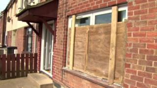 Window boarded up after it was smashed with brick