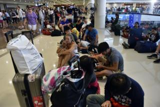 Passengers gather at the Gusti Ngurah Rai International airport in Denpasar, Bali on 27 November 2017, after flights were cancelled due to the threat of an eruption by the Mount Agung volcano.