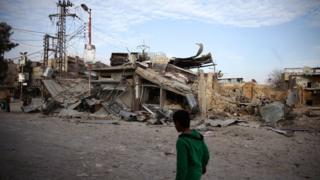 Criança caminha perto de construções danificadas por ataques na cidade de Douma