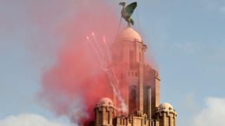 Flares spark out from the top of the Liver Building