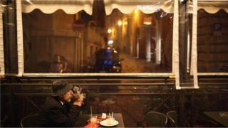 Homem em cafeteria, observando, sem fazer nada - il dolce far niente italiano