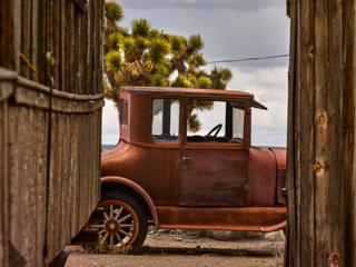 An abandoned car seen between two wooden buildings
