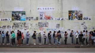 "People queue to cast their vote in front of a ""Lennon Wall"" adorned with tattered posters"