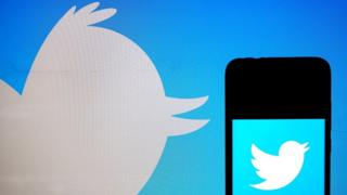 Technology Twitter logo on phone on background of Twitter logo