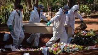 Employees carry the coffin of a person who died from Covid-19 in Sao Paulo, Brazil