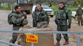 Israeli troops close a road in the southern Kibbutz of Mefalsim, near the border with Gaza, on 25 March 2019