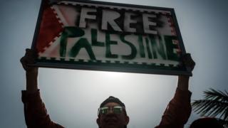 شخص يحمل لافتة كتب عليها فلسطين حرة