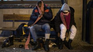 Migrants from Guinea don winter shoes and clothes donated by a charity organisation in Bardonecchia, Italy, 13 January 2018