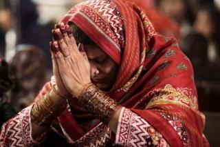 Sementara di Lahore, Pakistan, perempuan ini berdoa di altar.