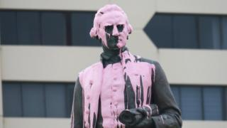 A statue of Captain Cook covered in pink paint