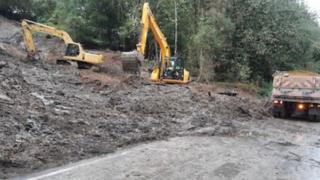 Two diggers and a truck on a landslide-hit road
