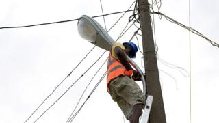 Electricity worker ontop pole