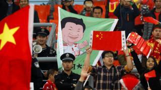 中国球迷举起国旗和习近平的漫画肖像