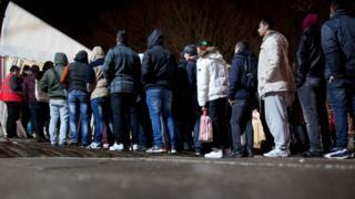 Asylum seekers queue up in Berlin at a registration centre in Berlin