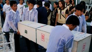 Funeral workers carry a crate containing the body of Joanna Demafelis in her hometown in Iloilo province in the Philippines on 17 February 2018.