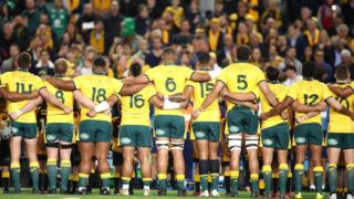Back view of the Australia's rugby team linking arms and singing the anthem at a test game