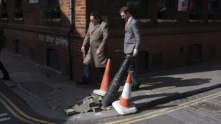 Men walking past a damaged pavement