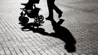 Silhouette of a parent pushing a pram