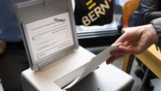A person casts his ballot paper into the ballot box at a polling station in Berne, Switzerland,