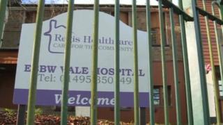 A picture of Regis Healthcare's sign behind a barred fence