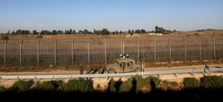 Israeli soldiers patrol the ceasefire line between Israel and Syria, as seen from the Israeli-occupied Golan Heights