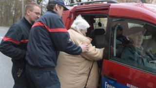 Des sapeurs pompiers Allemands évacuant des personnes âgées