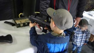 A photo from the event showing a young boy holding a military-style gun