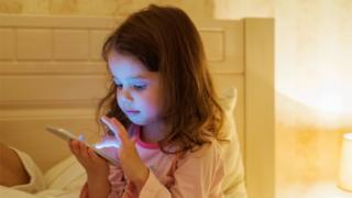Criança olhando para smartphones