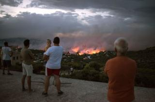 People watch a wildfire in the town of Rafina, near Athens