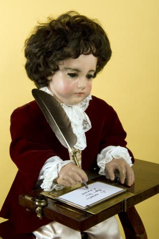 The figures are still working. The boy dips the quill in an inkwell and shakes off the extra ink before writing on the paper.