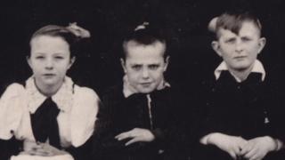 Tres niños en una foto antigua, en blanco y negro