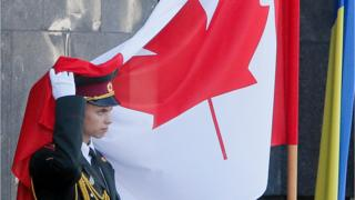 An Ukrainian soldier takes away the Canadian flag from his hat during a welcome ceremony in Kiev, Ukraine, Monday, July 11, 2016