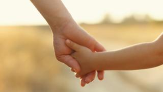 Close-up shot of man holding hands with a young girl
