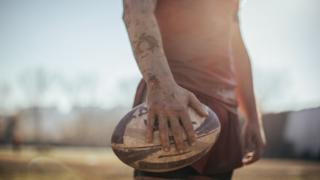 A rugby player holding a rugby ball