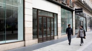 Two people walk down empty High Street